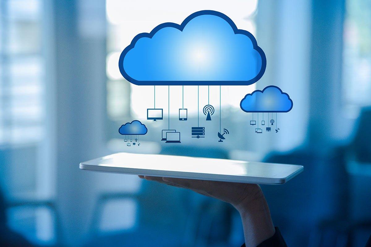 Um tablet sendo levantado sob nuvens, dando a ideia de tecnologia.